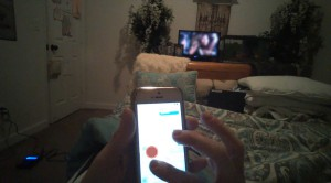 A participant in our eye-tracking study uses a smartphone while watching TV on a typical weeknight. The red dot indicates where her eyes were focused - Facebook IQ